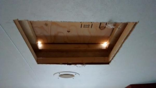 Cut hole in bedroom ceiling and drilled corner holes through roof.
