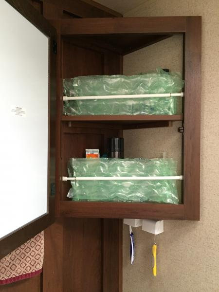 For traveling purpose only, we use an expandable curtain rod along with packaging bubbles to keep items in the medicine cabinet upright.