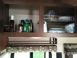 Spice rack above the window and shelves in the overhead cabinets.