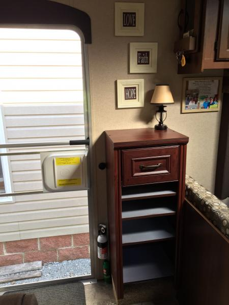 Installed a Closetmaid cabinet to store our shoes. If you look to the left of the cabinet you will see a dimmer switch, which is connected to the lamp, so we no longer have to walk into a dark trailer. We also mounted a push bar on the screen door.