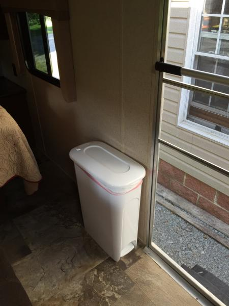 I found the perfect trash can at Lowe's. It is very narrow and not in the way when walking into the bedroom.