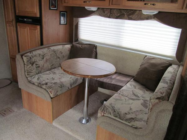"""I modified the dinette to include a """"pub table."""" I bought a 24"""" pine round from Lowes, stained it in Golden Oak and got 4 groutable self stick tiles in a sandstone to compliment the interior. Picked up an extra table base and I found some brown leatherette material at JoAnn's fabrics and a piece of 4"""" foam and used 3/4"""" plywood to make the seat extension across the back of the dinette."""