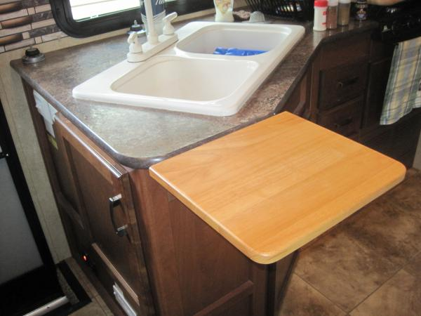 IMG 4783 Flip up cutting board mounted by sink for added work space.