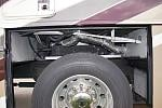 Driver's side wheelwell disassembled with gray tank exposed. Original KIB level indicators installed on this side.