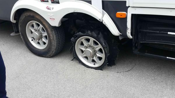Blown Towmax tire on RV (not Jayco). Note torn brake wire under door step.