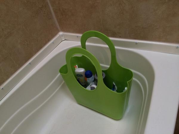 Dollar store plastic basket sits in the tub with shower goodies, extra sunscreen, etc inside.