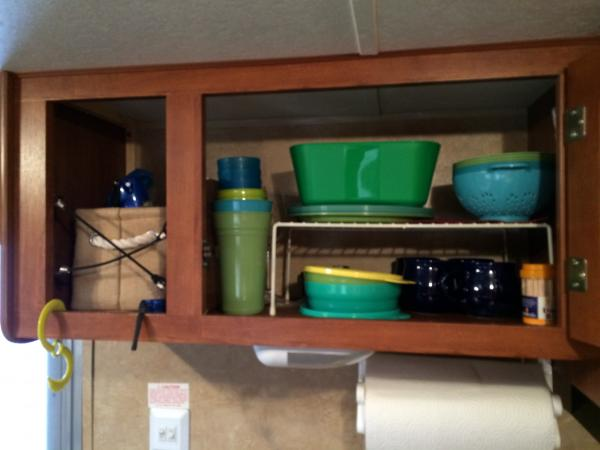 The dish cupboard.  We have a wire Rubbermaid rack to make storage more efficient.  We have the cheap cheap Walmart (do you see a theme? lol) picnic dishes.  They've lasted really well for the $1.50 we paid for a pack of six and they are super light.  We have a small set of glass coffee mugs that make a morning coffee so much nicer than out of a travel mug. We also have two acrylic wine glasses in case we want to get fancy!  We popped out the panel on the front of this cabinet to make a quick access spot for things like change for the shower house, bug spray, sun screen, the lighter for the stove/water heater/BBQ.  I didn't take a good shot, but will later.  We just used the light panel we removed, turned it on it's side inside the cabinet to keep the dishes from shifting.  Really light bungee cords X'd between staples left from the panel being popped out keep the burlap basket from sliding out in travel.