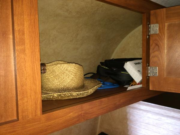 We store all of our clothing (mine and hubby's) above the dinette.  The far corners that are harder to reach get the stuff we use less often around the trailer - crank up radio, bags for short hikes/touristy stuff, umbrellas, and in my far corner the games are usually stored in a basket or under my cloths.