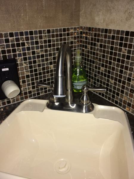We installed a smart tile backsplash in the bathroom, as well as a Glacier Bay gooseneck faucet so you can actually get your hands under the water! Cool feature - the faucet has a water-activated LED light!